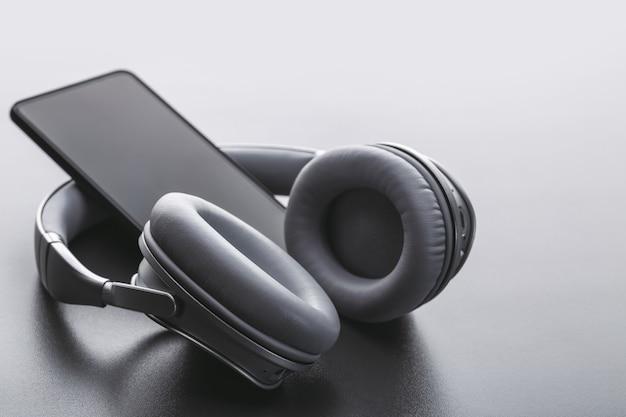 スマートフォンとbluetoothワイヤレスヘッドフォン。好きな音楽を聴いています。スタジオショット、灰色の背景。