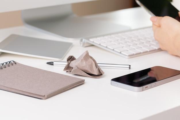 Смартфон и клавиатура компьютера на офисном столе крупным планом