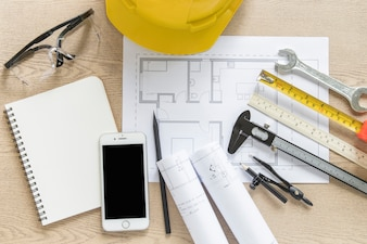 Smartphone and construction tools near draft