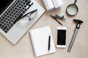 Smartphone and drafting supplies near laptop