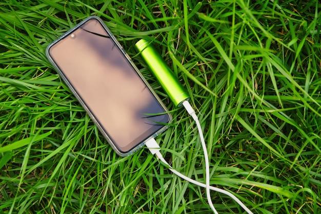 充電中にスマートフォンと外部電源バンクが公園の緑の芝生の上に横たわる