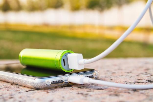 Смартфон и внешний блок питания лежат на гранитной поверхности в парке во время зарядки