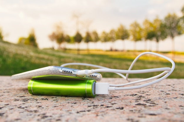 充電中、スマートフォンと外部電源バンクが公園の花崗岩の表面にあります