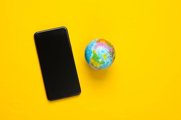 黄色い表面にスマートフォンと地球儀。グローバルネットワーク。世界中のモバイル通信。 5gグローバルネットワーク