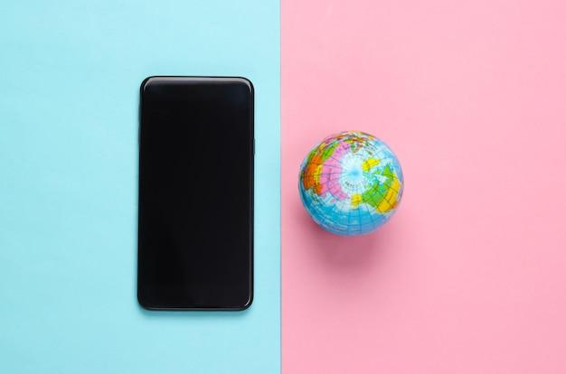 ピンクブルーの表面にスマートフォンと地球儀。グローバルネットワーク。世界中のモバイル通信。 5gグローバルネットワーク