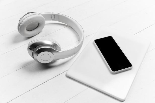 スマートフォンとヘッドホン。空白の画面。白色の表面にモノクロのスタイリッシュでトレンディな構成。上面図、フラットレイ。周りのいつものものの純粋な美しさ。広告のコピースペース。