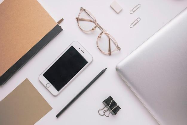 Смартфон и ноутбук среди канцелярских принадлежностей