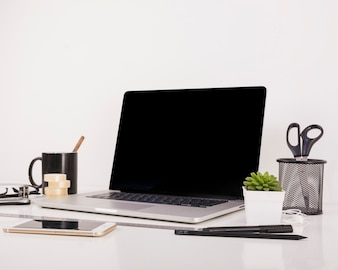 Smartphone and laptop with blank black screen on office desk