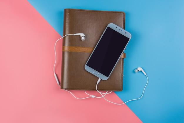 青とピンクのスマートフォンとノートブック