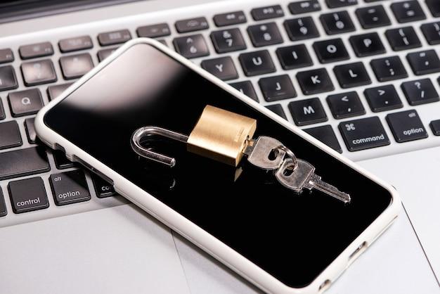 スマートフォンと南京錠はノートパソコンのキーボードの上に横たわっています
