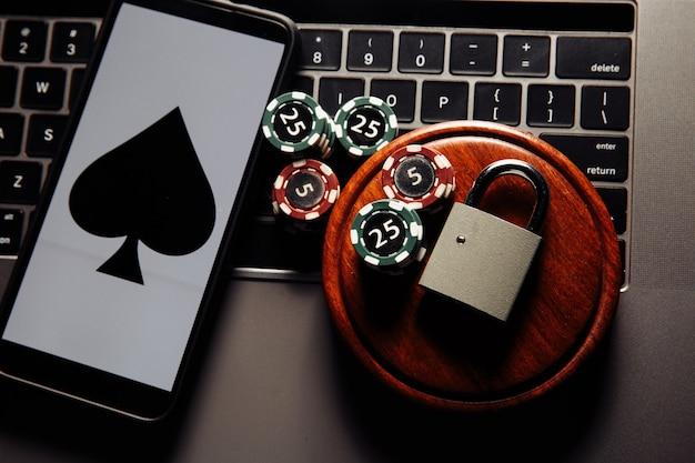 スマートフォンと南京錠、ポーカーチップ、ノートパソコンのキーボードのトランプ。法の概念とギャンブルの規制