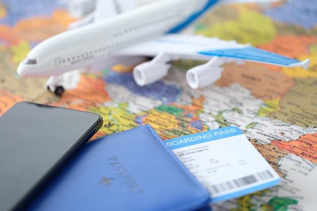 티켓이 있는 스마트폰과 여권은 작은 비행기 예약 및 검색을 통해 세계 지도에 있습니다.