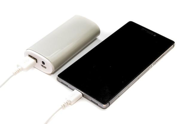 白い背景で隔離のスマートフォンとパワーバンク