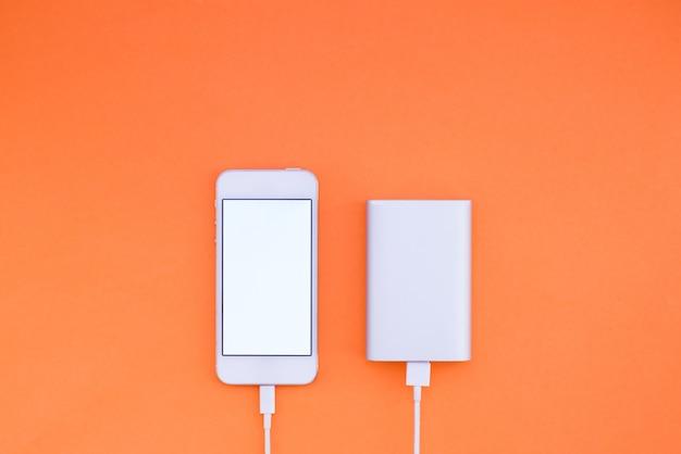 オレンジ色の背景にスマートフォンとpowerbank。 powerbankは壁に電話を充電します。フラットレイ