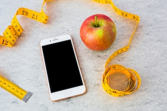 Smartphone and red ripe apple with yellow measuring tape on gray textured background