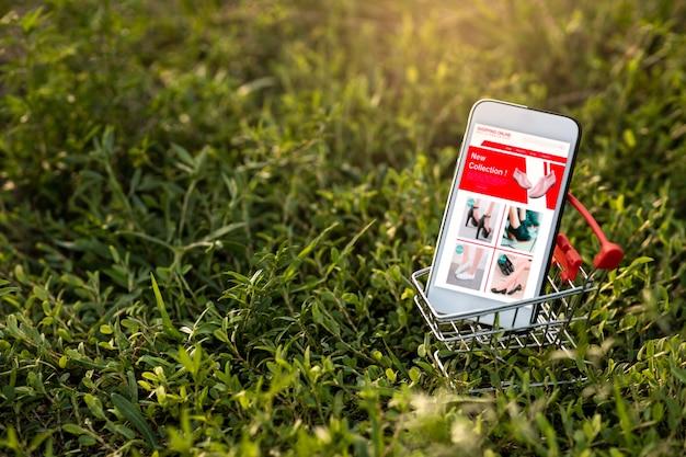 Смартфон и корзина на зеленой траве. покупки онлайн или концепции электронной коммерции на веб-сайте для окружающей среды.