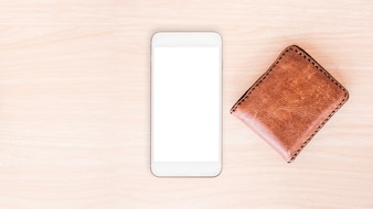 Smartphone and wallet on wood table background.