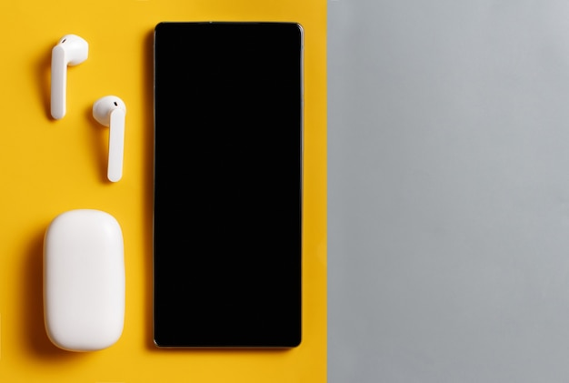 회색 및 노란색 배경에 케이스가 있는 스마트폰 및 흰색 무선 이어폰, 위쪽