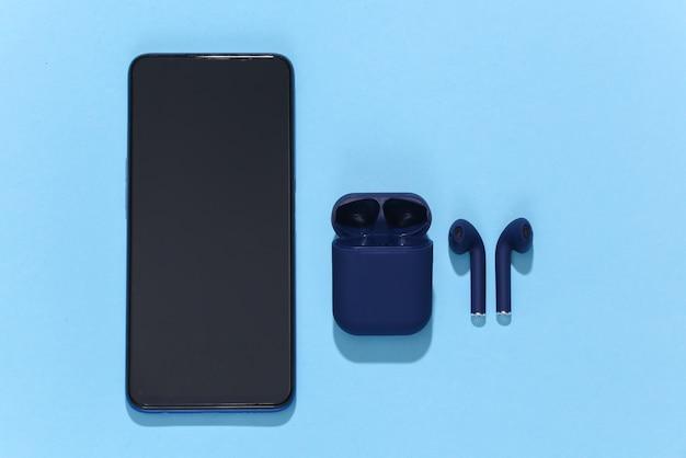 スマートフォンとワイヤレスbluetoothヘッドフォンまたは充電ケース付きイヤフォン