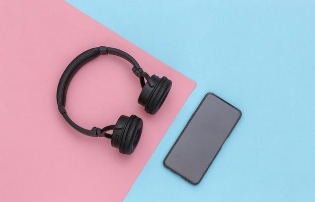 ピンクブルーのパステルカラーの背景にスマートフォンとワイヤレスステレオヘッドフォン。上面図