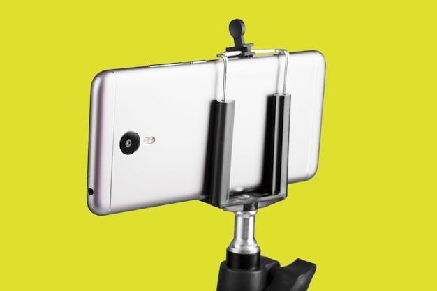 Смартфон, прикрепленный к штативу на желтой поверхности