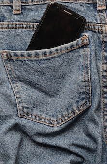 Smartphone in the back pocket of crumpled jeans