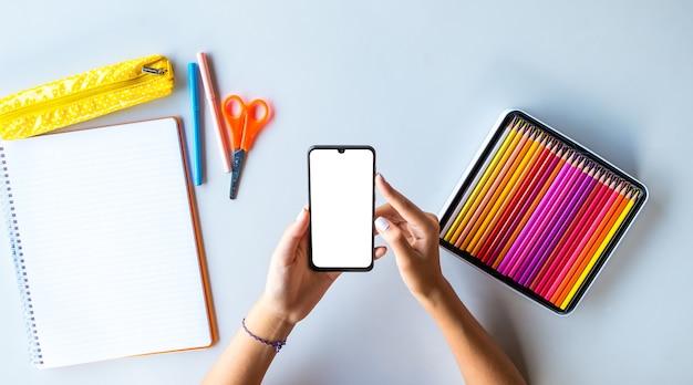 Смартфон обратно в школу с пустым экраном с руками подростка и цветными карандашами настройка