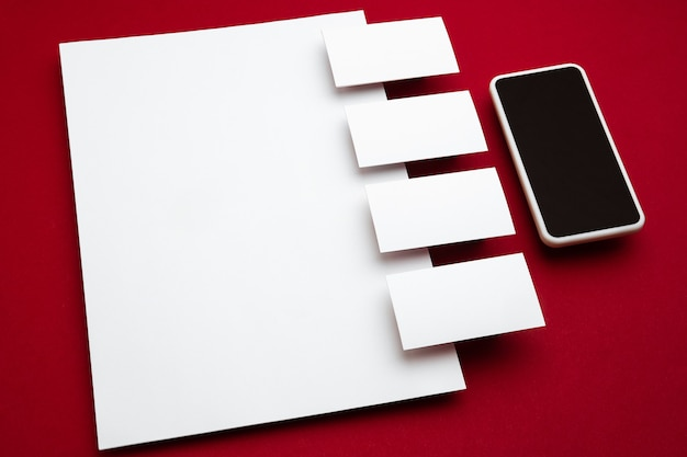 Smartphone and blank flyer posters and cards floating above red background. office styled, modern mockup for advertising, image or text. blank white copyspace for design, business and finance concept.
