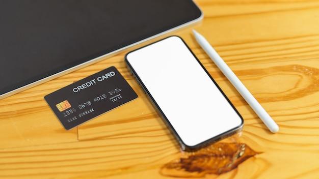 나무 테이블에 신용 카드 태블릿과 스타일러스 펜으로 광고를 위한 스마트폰 빈 화면
