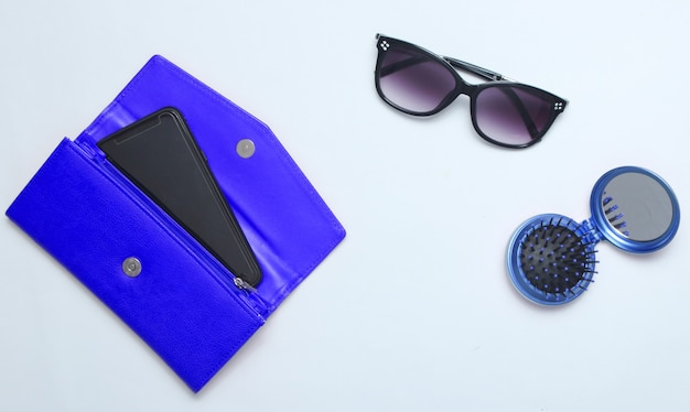 Smartphone in blue leather wallet, sunglasses, mirror hairbrush