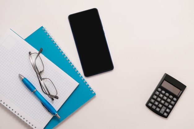 Smartphone blue notebook glasses pen top view