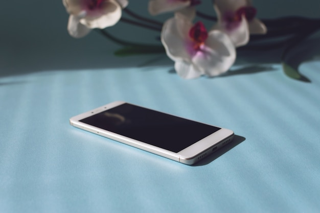Smartphone on a blue table with flowers