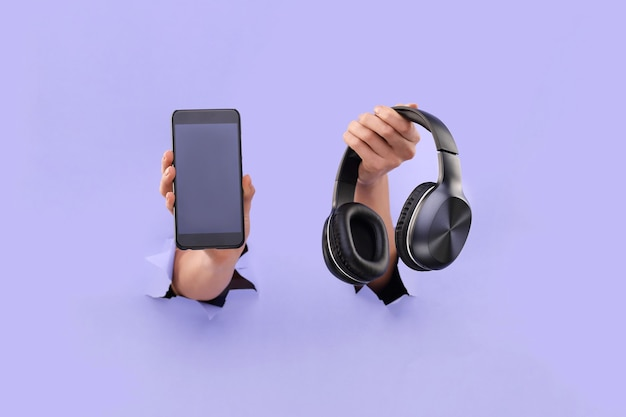 Smartphone and bluetooth headphones stick out from a blue torn