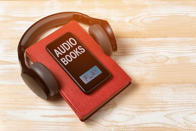 スマートフォン、本、ヘッドホン。お使いの携帯電話で本を聞いてください。オーディオブックのコンセプト。