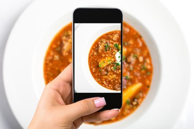 Смартфон камера рука точка стрелять фото суп. фотография еды. сделано для социальных сетей. мобильный телефон вид сверху