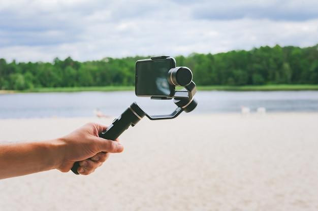 남자의 손에 있는 스마트폰 카메라 안정기. 모래 해변과 호수가 있는 자연을 배경으로.