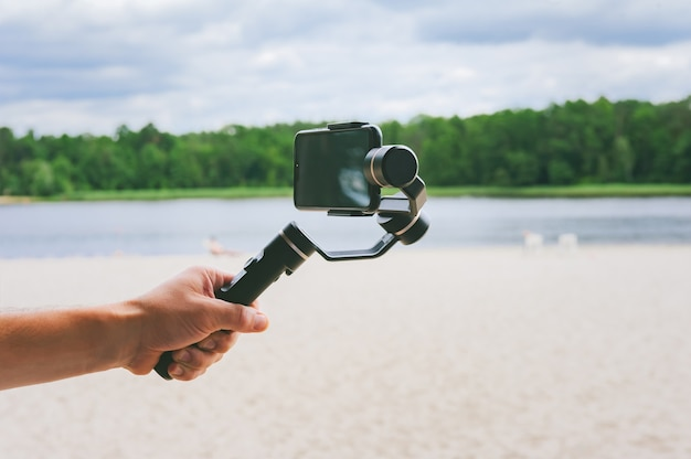 Smartphone camera stabilizer in a man's hand. against the backdrop of a sand beach and nature with a lake.