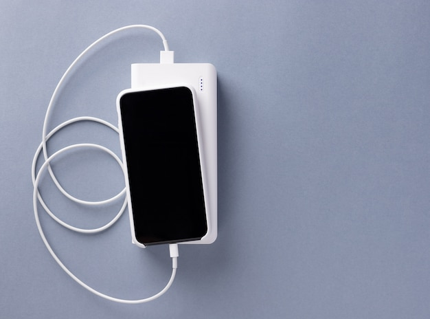 Smartphone charged via a usb cable from the power bank charger