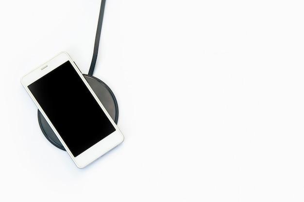 白のワイヤレス充電器で充電するスマートフォン