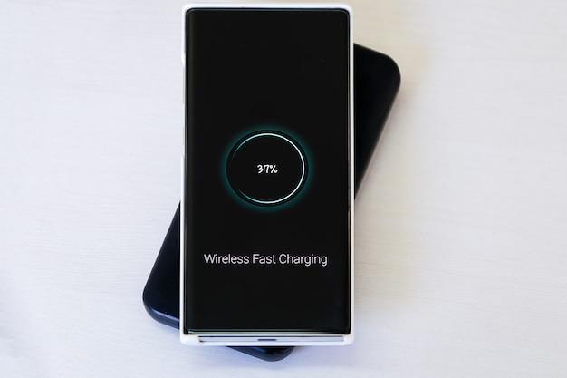 Зарядка смартфона на портативном быстром беспроводном зарядном устройстве - новая технология