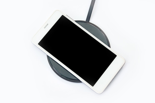 Smartphone charging on a wireless charger on white