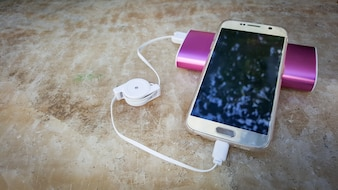 Smartphone charging with pink power bank on the stone table background