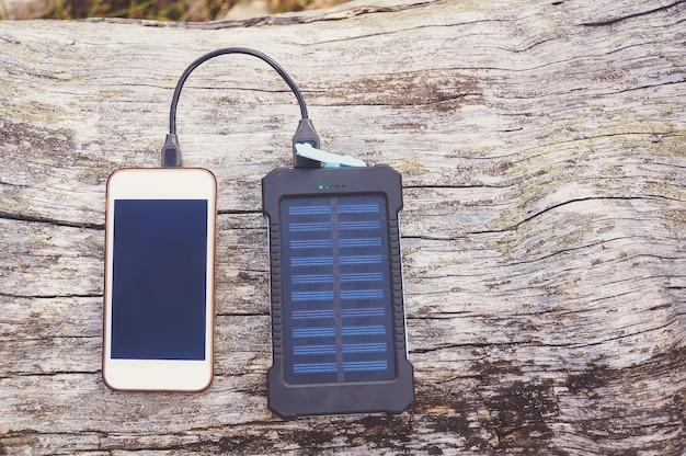 木の背景、セレクティブフォーカス、ソフトフォーカスに太陽電池を搭載したピンクのパワーバンクでスマートフォンを充電