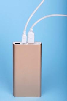 青い背景の上のパワーバンクで充電するスマートフォン。