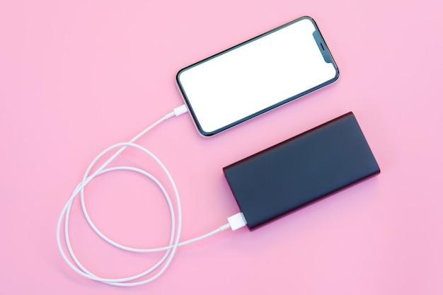 분홍색 배경에 전원 은행으로 충전하는 스마트폰. 복사 공간을 위한 클리핑 패스가 있는 흰색 화면 또는 빈 화면. 플랫 레이