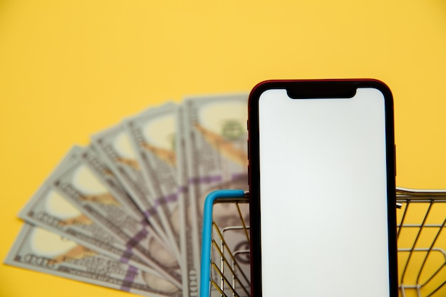 Smartphone close-up, metal market basket and banknotes of dollars on yellow