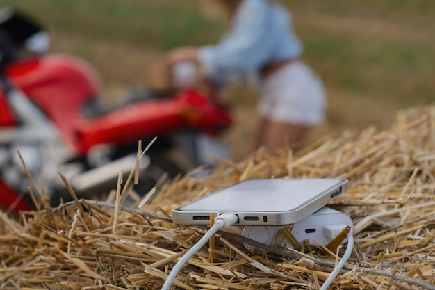 휴대용 충전기로 스마트폰 클로즈업. power bank는 오토바이, 소녀 및 자연을 배경으로 전화를 충전합니다.