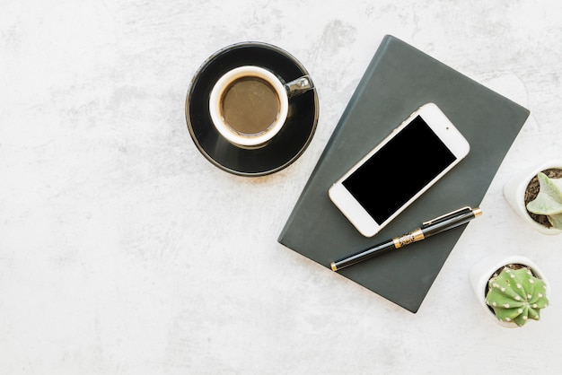 Smartphone and coffee on table with notebook
