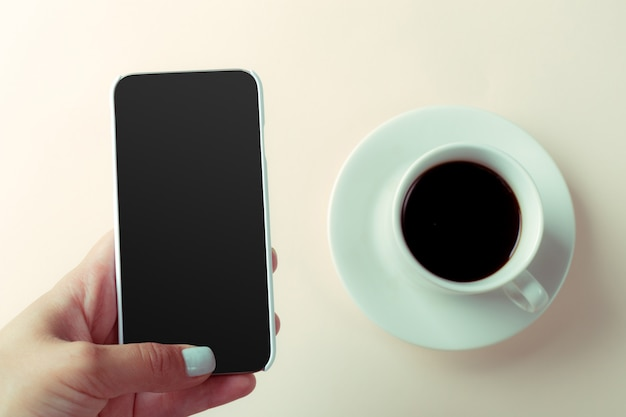 Smartphone and coffee on the table