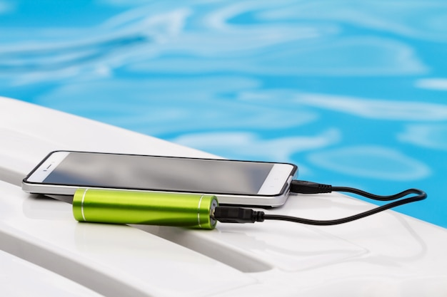 Smartphone connected to the green portable battery charger through usb cable on blue water background.